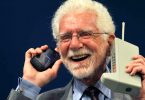 U.S. engineer Martin Cooper holds the Motorola DynaTAC phone, the world's first commercial handheld cellular phone, and his current mobile phone during a news conference in Oviedo